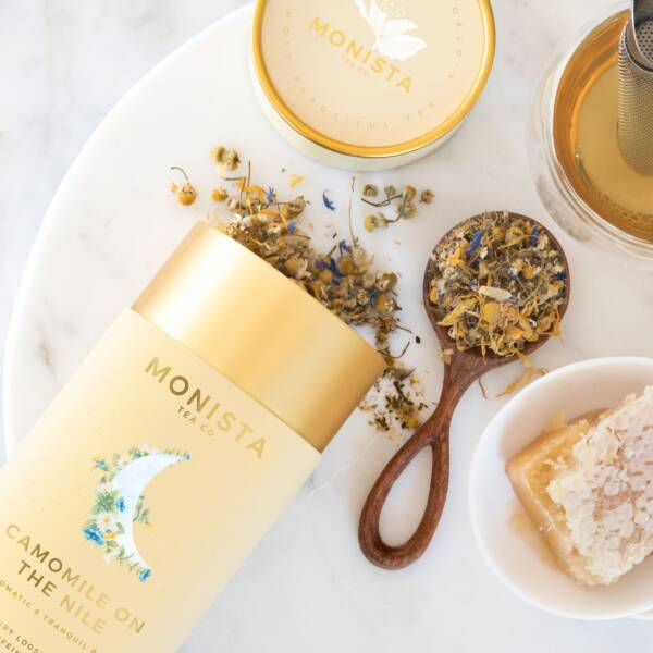 Camomile Tea on a spoon with honey and yellow canister