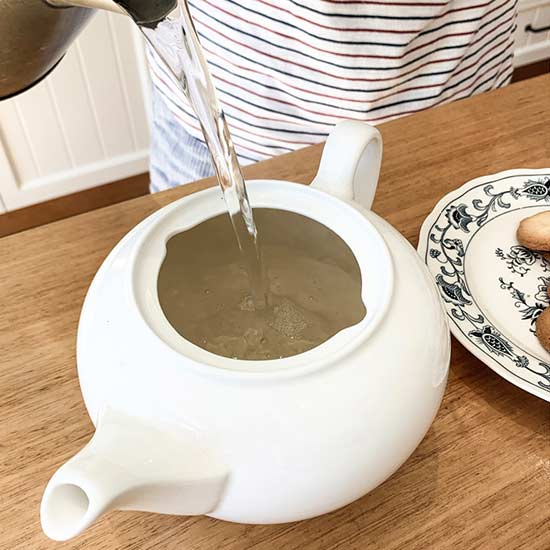 Filling tea pot with hot water