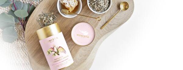Matilda's Lemongrass and ginger pink tea canister laying down with honey and spoon